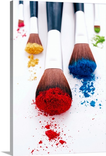 Brightly coloured eyeshadow powders on eyeshadow brushes, close-up