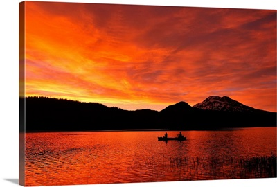 Canoeing in a mountain lake at sunset.