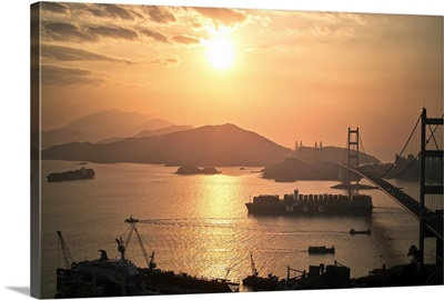 Cargo vessel crossing the bridge at sunset.