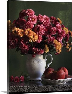 Chrysanthemums flowers in vase with red apples in plate.