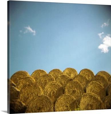 circular hay bales against blue sky with small white clouds.
