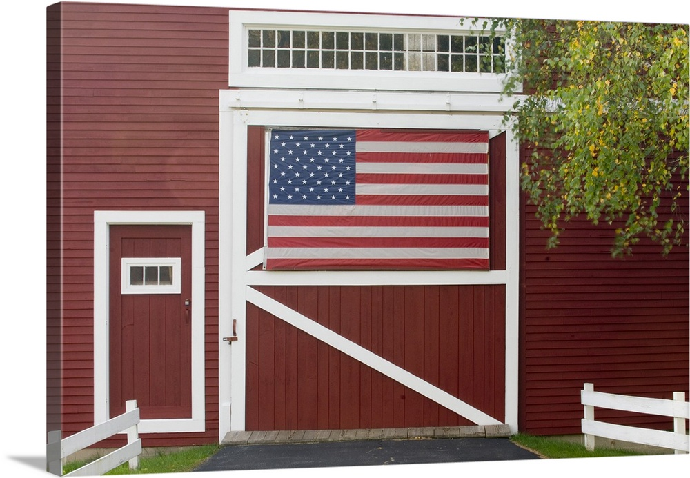 Classic New England Farm With Red Barn And White Fence, American Flag On  Barn Door
