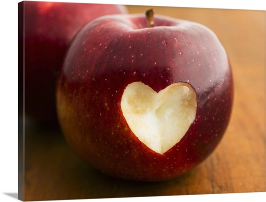 Close up of apple with missing bite in heart shape, studio shot