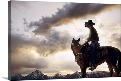 Cowboy on horse looking at mountain range, dusk, low angle view