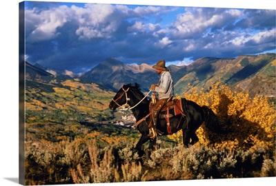 Cowboy riding along ridge above town, Snowmass, Colorado
