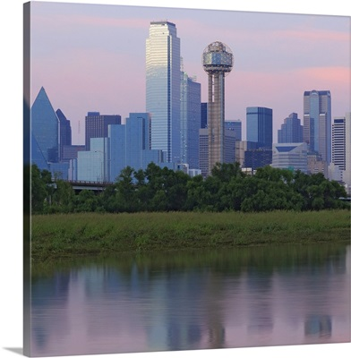 Dallas skyline reflected in water at sunset.