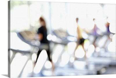 Defocused view of people on treadmills in health club
