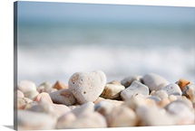 Directed focus on a heart shaped stone on a pebble beach in the foreground.