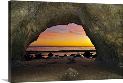 Dramatic sunset seen from inside cave on beach.
