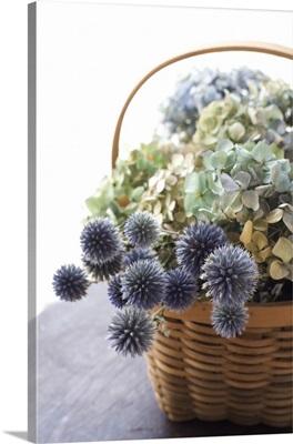 Dried flowers in wooden basket.