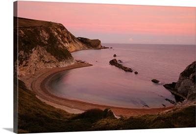 Dusk falls over Man Of War Bay on Dorset's Jurassic Coast.