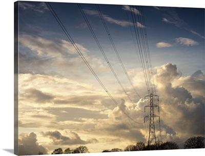 Electric high power lines against beautiful cloud formation.