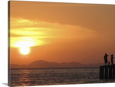Family watching sunset from jetty in Malaysia.