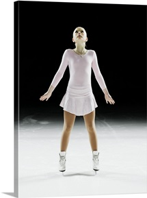 Female figure skater, arms out, looking up