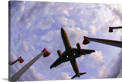 Fisheye wide shot of an airplane landing directly over the viewer