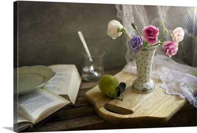 Flower vase and pear on board and books on table.