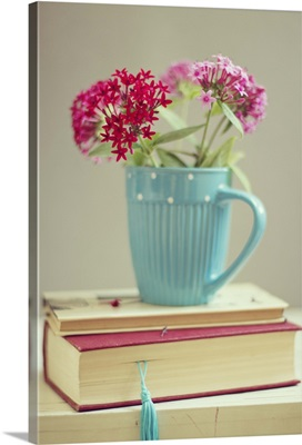 Flowers in blue cup on two books.