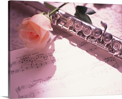 Flute next to sheet music and pink rose