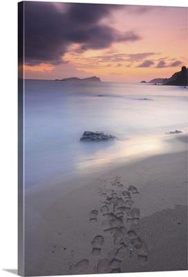 Footprints on beach at sunset.