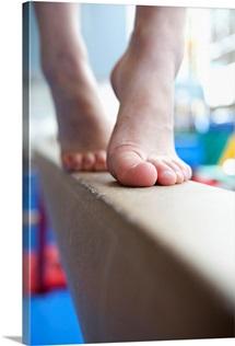 Girl slowly walks across balance beam on her toes, close up of feet
