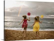 Girls running on beach holding windmills