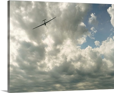 Glider in flight against cloudy sky, low angle view