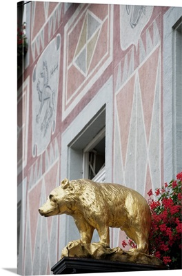 gold bear sculpture with flowers and a painted building