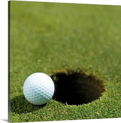 Golf ball on the edge of the hole