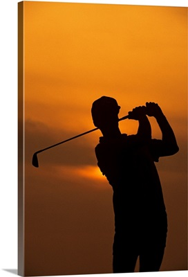 Golfer silhouetted by sunset