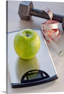 Green apple on weight scale, tape measure and exercise weight in background