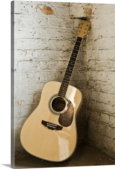 Guitar leaning against brick wall