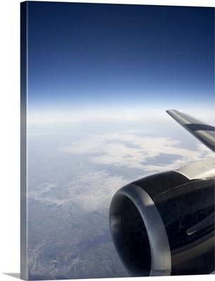 High altitude view of a jet engine set against a gentle cloudscape