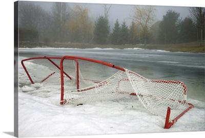 Hockey net left from season in melting snow at Ottawa, Ontario, Canada.