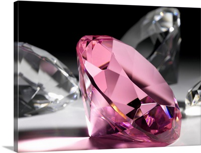 Large pink diamond surrounded by clear diamonds, close-up (still life)