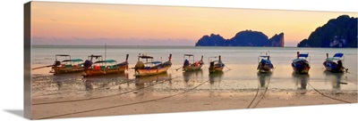 Long tail boats on beach at sunset.