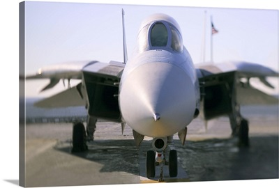Looking straight on at the nose of an F-14 military aircraft at the airport.