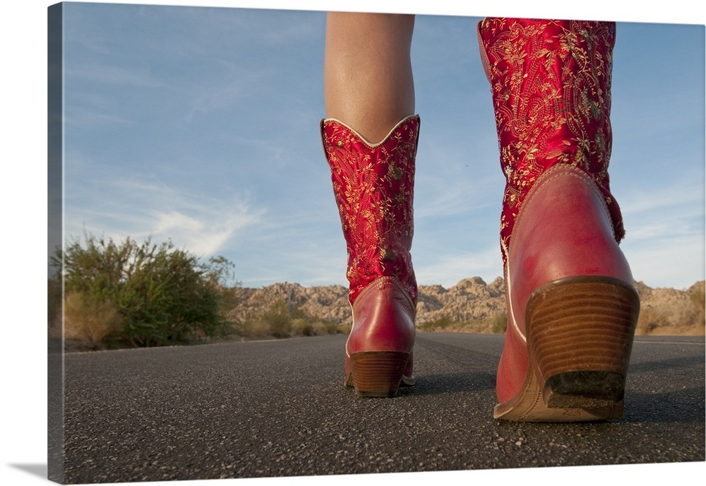 Low Angle View Of Woman Wearing Cowboy Boots Walking On Desert Road