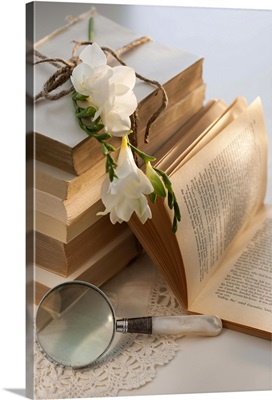 Magnifying glass beside stack of books with flowers