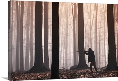 Man aiming shotgun in forest