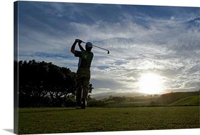 Mature man swinging golf club at dusk