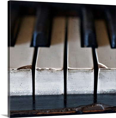Old, antique upright piano keys displaying wear and tear.