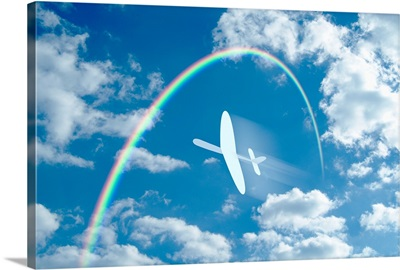 Paper airplane flying through a blue sky and clouds towards a rainbow
