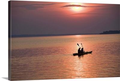 People kayaking at sunset