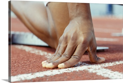 Person kneeling with hands on starting line, Close up of hand