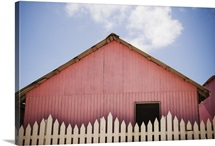 Pink house behind a white picket fence