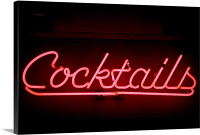 Pink neon cocktails sign against black background, close-up