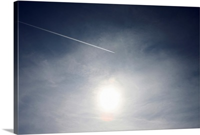 Plane and Vapor trail flying above sun.