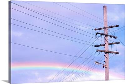 Powerlines against rainbow sky.