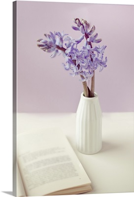 Purple flower vase with open book on table.