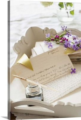 Quill pen with letters and flowers